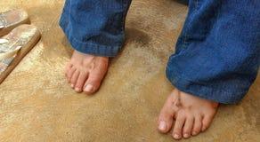 Vuile meisjes` s voeten die met wipschakelaars naast haar na het werken in de tuin rusten stock afbeeldingen