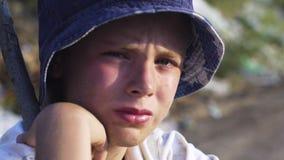 Vuile onder ogen gezien jongen die ver weg in stortplaats kijken stock footage