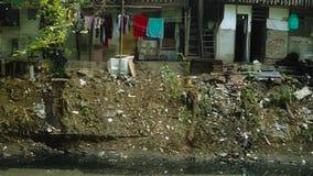 Vuile rivier en huizen van armen stock footage