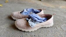 Vuile schoenenvrouw en sokken op cementvloer stock afbeelding