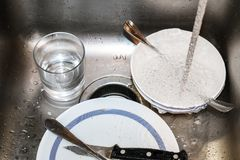Vuile schotels in roestvrij staalgootsteen met water die binnen - selectieve nadruk lopen royalty-vrije stock afbeeldingen