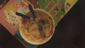 Vuile Tomatensaus Bevlekte Kom met Vork en Lepel - Kleurrijke Lijst stock foto