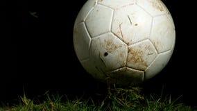 Vuile voetbal die op gras stuiteren stock videobeelden
