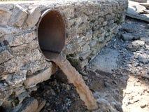 Vuile waterstromen van een bruine roestige rioolpijpen royalty-vrije stock afbeeldingen