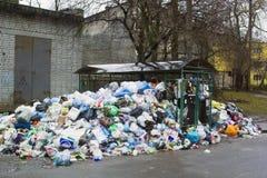 Vuilnisbakken van groot hoophuisvuil worden behandeld op stadsstraat die Royalty-vrije Stock Foto
