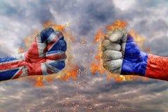 Vuist twee met de vlag van Rusland en het Verenigd Koninkrijk bij elkaar onder ogen die wordt gezien die royalty-vrije stock afbeelding