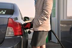 Vul de auto met brandstof Bijtankend kanon in tankvuller stock afbeelding
