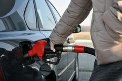 Vul de auto met brandstof de vrouw bij een benzinestation met een verbonden vinger plooit de auto stock foto's