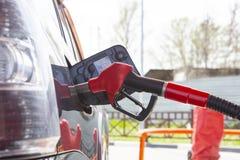 Vul de auto met brandstof De auto wordt gevuld met benzine bij een benzinestation De pomp van het benzinestation Mensen bijtanken royalty-vrije stock foto