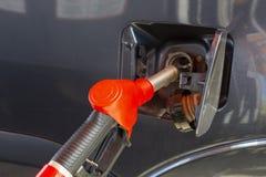 Vul de auto met brandstof De auto wordt gevuld met benzine bij een benzinestation De pomp van het benzinestation Mensen bijtanken royalty-vrije stock afbeelding