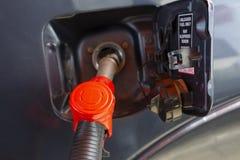Vul de auto met brandstof De auto wordt gevuld met benzine bij een benzinestation De pomp van het benzinestation Mensen bijtanken stock afbeeldingen