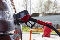 Vul de auto met brandstof De auto wordt gevuld met benzine bij een benzinestation De pomp van het benzinestation Mensen bijtanken royalty-vrije stock fotografie