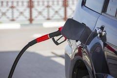 Vul de auto met brandstof De auto wordt gevuld met benzine bij een benzinestation De pomp van het benzinestation Mensen bijtanken stock fotografie
