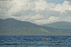 Vulcão atrás do barco indonésio do pescador no paraíso tropical Fotografia de Stock Royalty Free