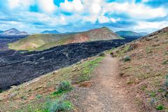 Vulcanic landscape with lava field and tourist road trail to vulcano Caldera Blanca, Lanzarote, Canary Islands, Spain.  royalty free stock images