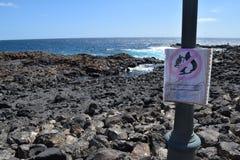 Squirrel warning on coast, Fuerteventura, Canary Island. Vulcanic stones on coast and sea waves on Fuerteventura island, near Caleta de Fuste. Canary Island royalty free stock photo