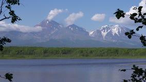 Vulcano attivo di stordimento, supporto di riflessione in lago alpino e nuvole in cielo blu video d archivio