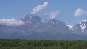 Vulcano, lago alpino, nuvole che vanno alla deriva attraverso il cielo blu vicino alle montagne di estate archivi video