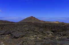 Vulkaan en een lavavlakte Stock Foto
