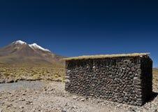 Vulkaan en een steenhut Stock Afbeeldingen