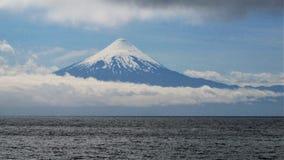 Vulkan i Sydamerika över sjön och molnen royaltyfri foto