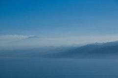 Vulkan und Berge im Nebel. Lizenzfreies Stockbild