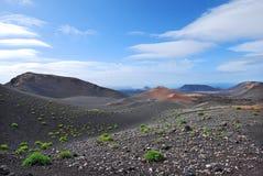 Vulkanisch berglandschap in Lanzarote, Canarische Eilanden. Blauwe hemel en wolken in de horizon. Stock Afbeeldingen