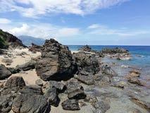 Vulkanische Felsen auf Seeufer stockbild