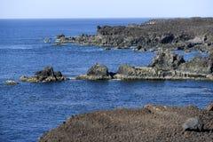 Vulkanische Felsen, die von der Einschätzung an der Küste von Th hervorstehen Stockbild