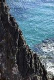 Vulkanische Felsen, die von der Einschätzung an der Küste von Th hervorstehen Lizenzfreie Stockbilder