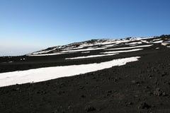 Vulkanische grond, sneeuw en hemel op de bovenkant van Etna Stock Foto