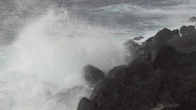 Vulkanische kustlijn en golven die, super langzame motie breken stock videobeelden