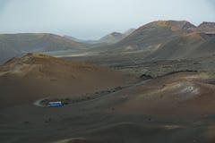 Vulkanische Landschaft, Lanzarote, Spanien, Krater, blauer touristischer Bus Lizenzfreie Stockfotografie