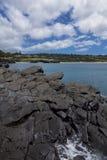 Vulkanische rotsdagzomende aardlaag bij oceaankust Stock Foto