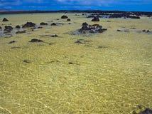 Vulkanische rotsen in groen water van een stille baai dichtbij de oceaan Glans op het Water Golven van de wind royalty-vrije stock fotografie