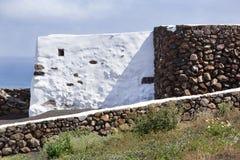 Vulkanische Steine und weiße Wände konkreten Errichtens lizenzfreie stockfotos