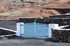 Vulkanische Steine zäunen Wand mit blauem hölzernem Tortor ein lizenzfreies stockfoto