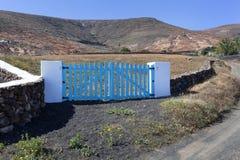 Vulkanische Steine zäunen Wand mit blauen hölzernen Tortoren ein stockbilder