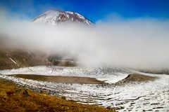 Vulkanisches Tal mit der Spitze von aktiver Vulkan Berg Ngauruhoe bedeckt durch mystischen Nebel und Schnee, Neuseeland, Tongarir lizenzfreie stockfotos