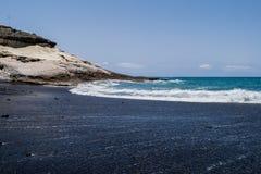 Vulkanisk strand för svart sand med havssikten i Tenerife, kanariefågelöar Fotografering för Bildbyråer