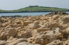 Vulkaniska stenar på en sandig strand av Praia da Ilha gör Pessegueiro, Portugal Royaltyfri Bild