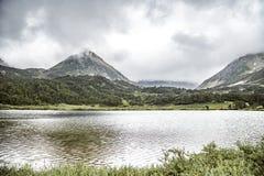Vulkaniskt landskap med gröna slättar och sjön på den Kamchatka halvön, Ryssland arkivbilder