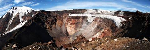 Vulkankrater med berg som täckas med snow på bakgrunden royaltyfria bilder