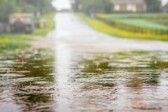 Vulklei met water op de weg tijdens de douche Sterke regen  stock afbeelding