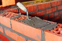 Vulklei op baksteen met cement Stock Foto's