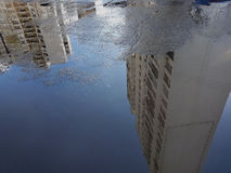 Vulklei: op de oppervlakte van het blauwe water zijn weerspiegeld wit vele verdiepingsgebouwen, op de linkerbodem is er een lege  Royalty-vrije Stock Foto's