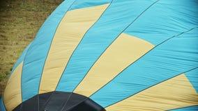 Vullend de luchtballon met hete lucht die brandmachine met behulp van - gele en blauwe gekleurde strepen op de ballon stock footage