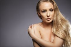 Vulnerable. Close up portrait of young woman topless covering her breast with her hand. Young vulnerable female model with long blond hair looking at camera stock photos