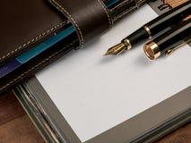 Vulpen en notitieboekje op lijst Stock Fotografie