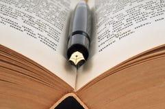 Vulpen op een boek wordt geplaatst dat royalty-vrije stock afbeeldingen